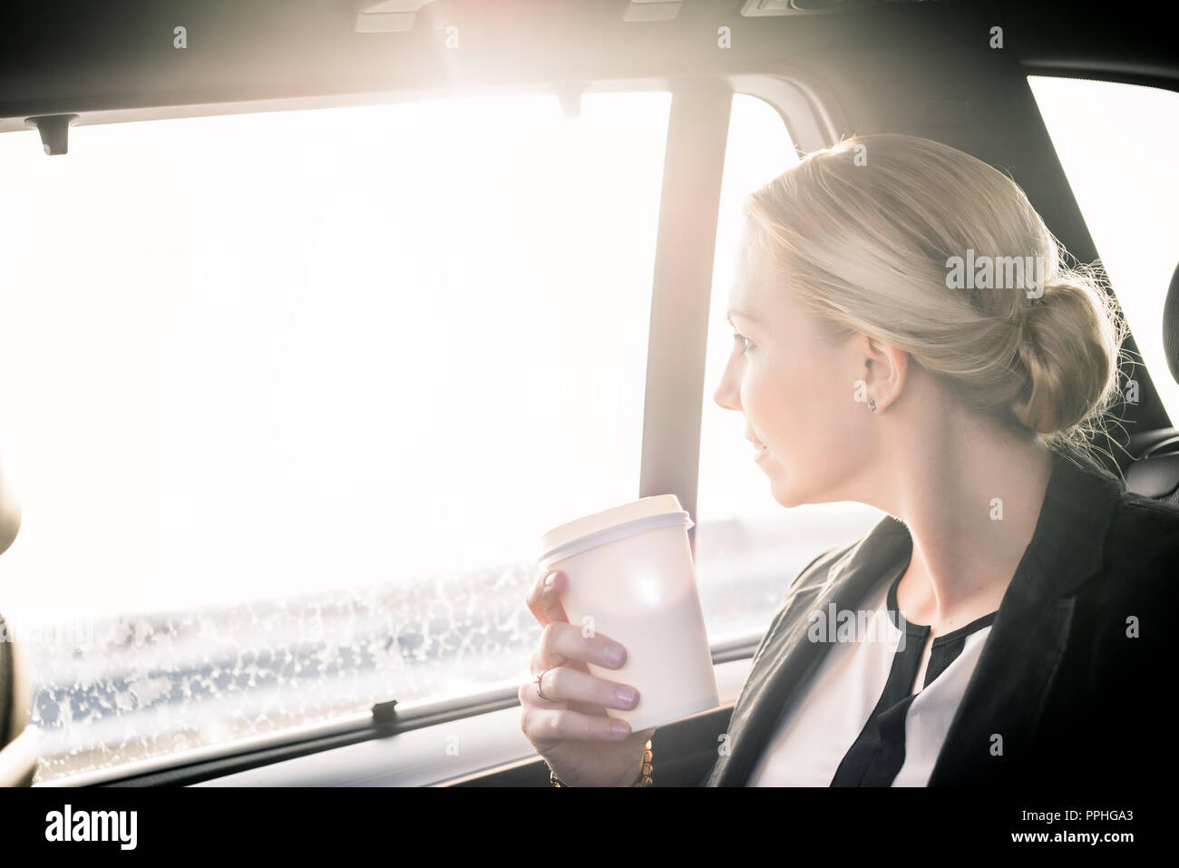 Businesswoman holding takeaway coffee cup in car - Stock Image