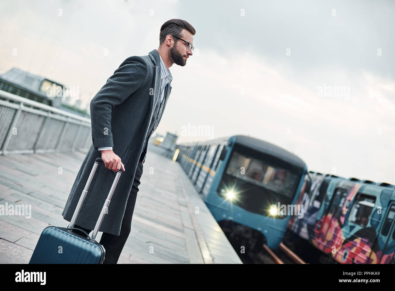 Business trip. Young businessman standing near railway with luggage waiting for train - Stock Image