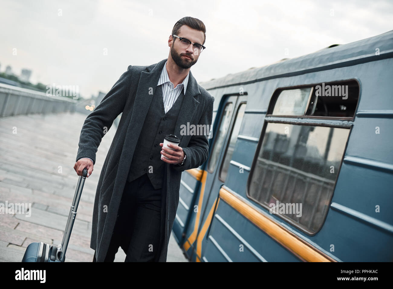 Business trip. Young businessman walking near railway with luggage holding cup drinking hot coffee - Stock Image