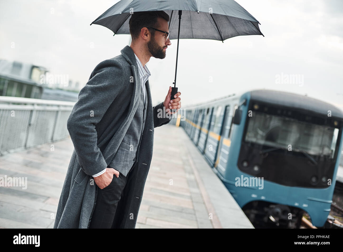 Waiting for train. Young businessman standing near railway under umbrella - Stock Image