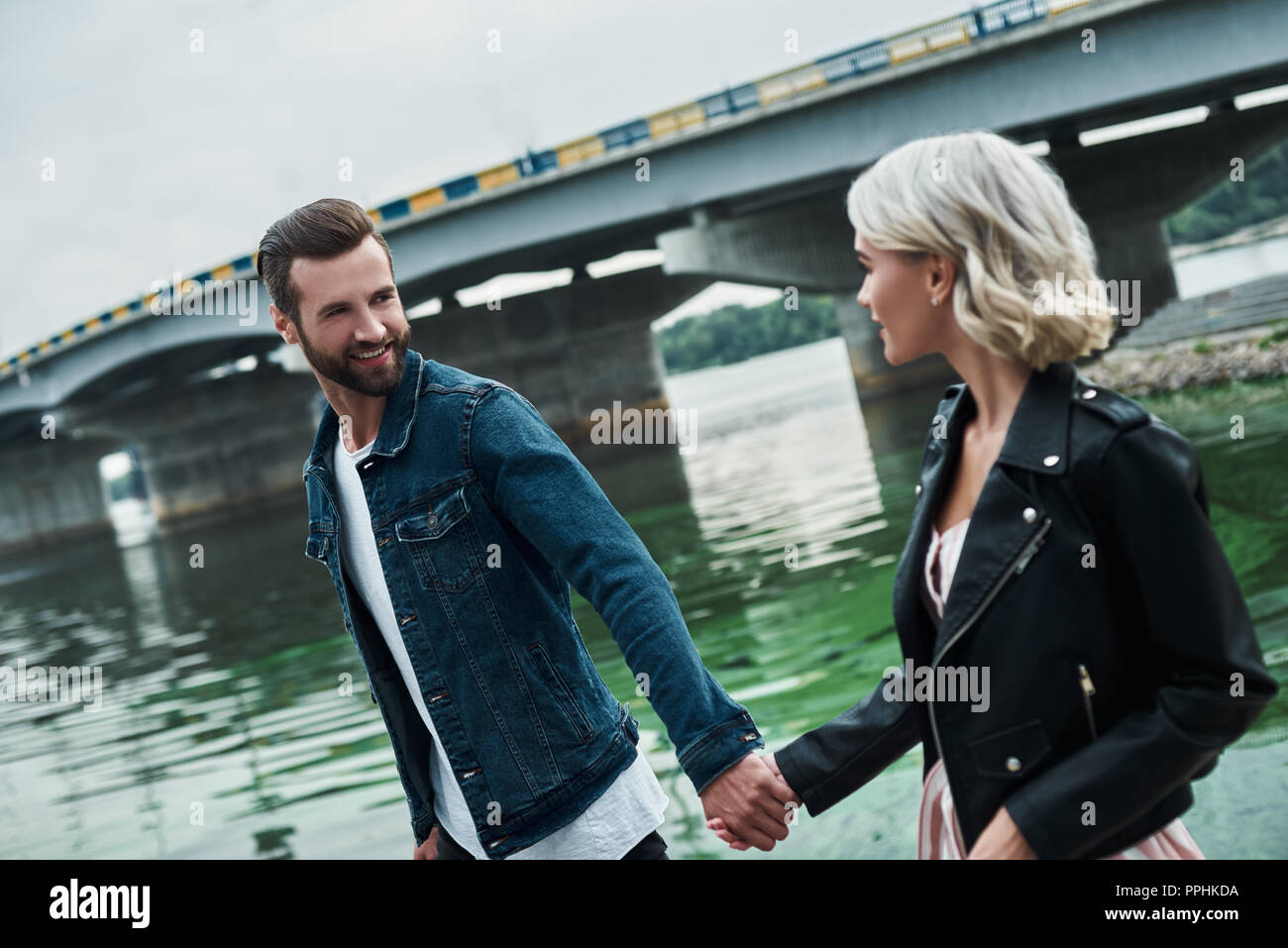 Romantic date outdoors. Young couple walking on the city street near water holding hands looking at each other talking smiling joyful - Stock Image