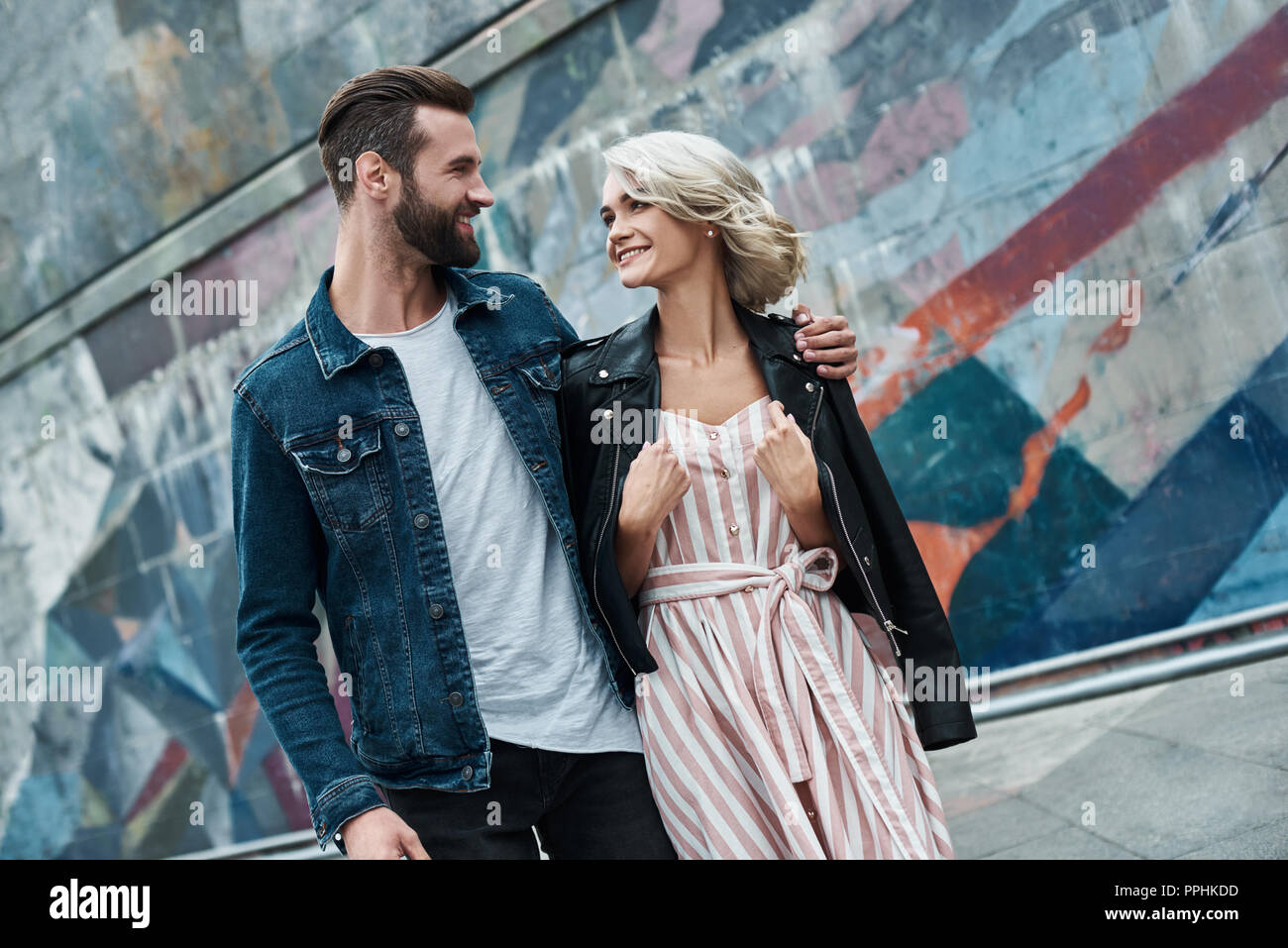 Romantic date outdoors. Young couple walking on the city street hugging looking at each other smiling cheerful - Stock Image