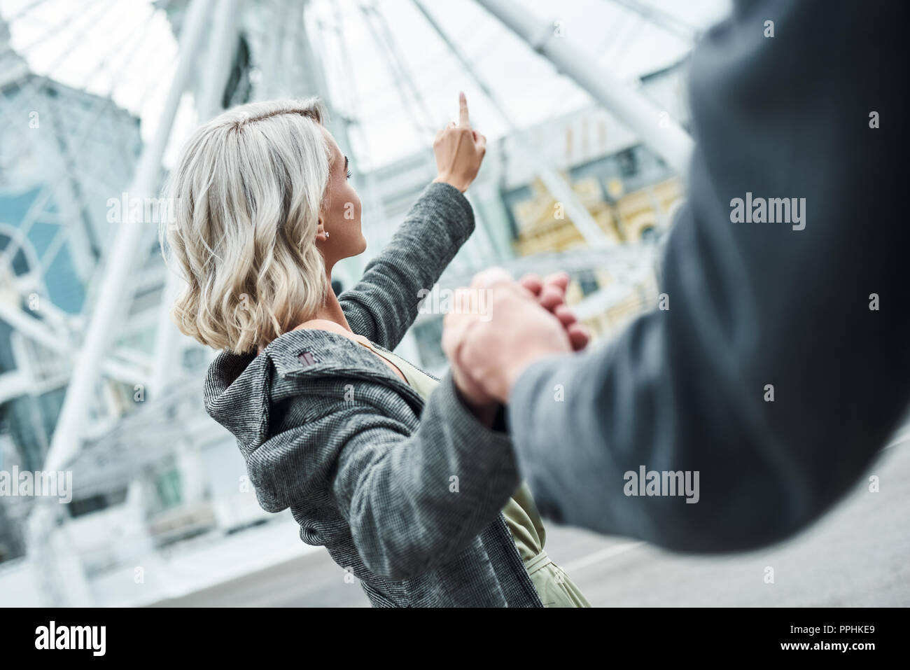 Romantic date outdoors. Young couple walking at entertainment park holding hands woman close-up pointing at ferris wheel excited - Stock Image