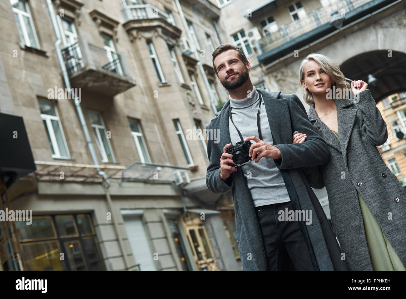 Romantic date outdoors. Young couple walking on the city street taking photos on camera smiling excited - Stock Image
