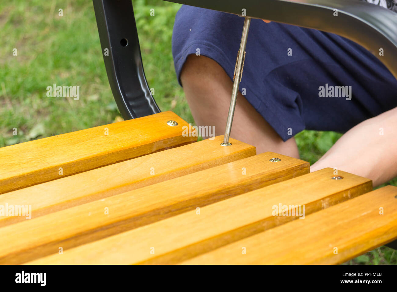 A man screwing a screw into the bench - Stock Image