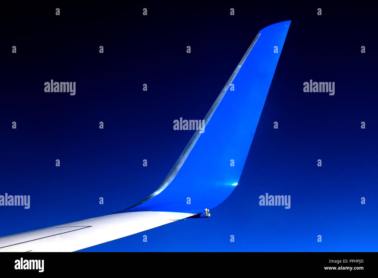 The blue winglet on a wing of plane when a flight in a blue sky. Part of jet wing, close view. - Stock Image