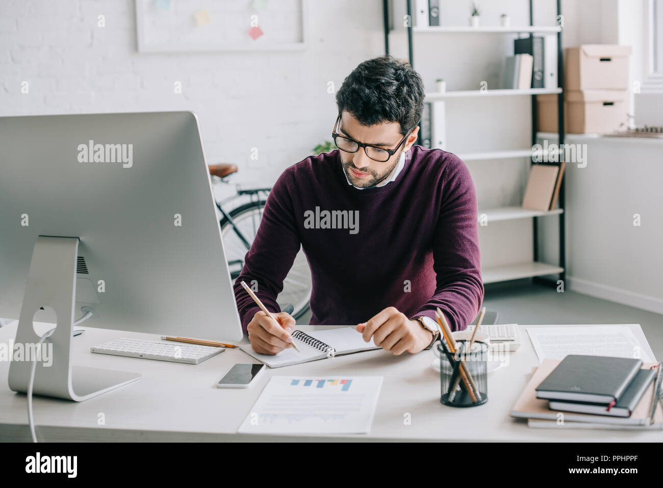 handsome designer in burgundy sweater writing something to notebook in office - Stock Image