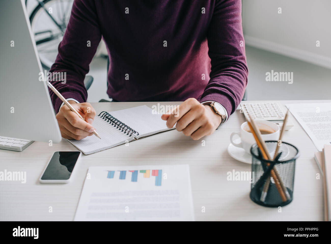 cropped image of designer in burgundy sweater writing something to notebook in office - Stock Image