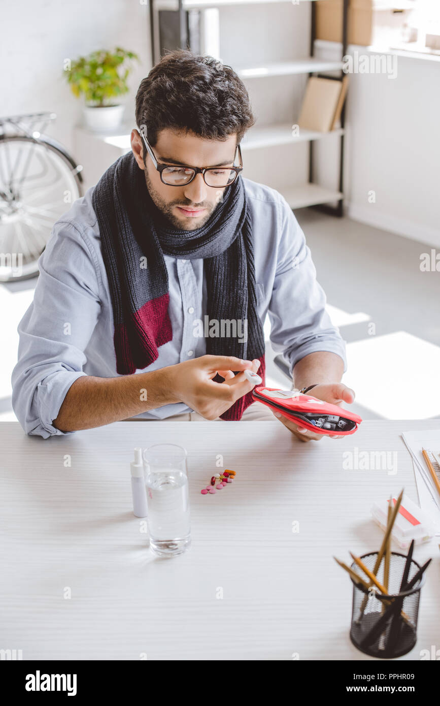 sick manager in scarf holding first aid kit and electronic thermometer in office - Stock Image