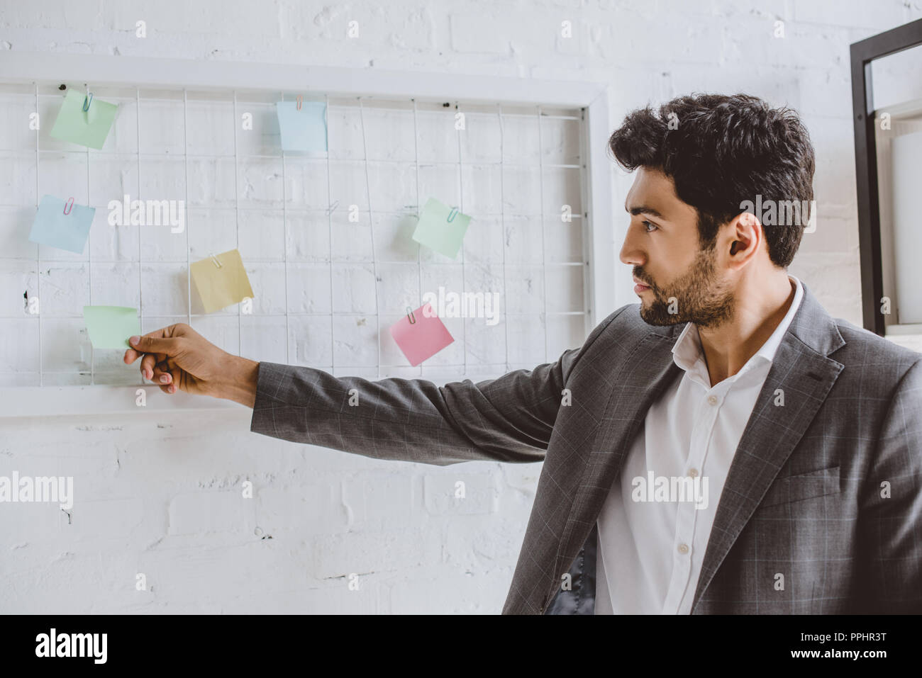 handsome businessman taking sticker from task board in office - Stock Image