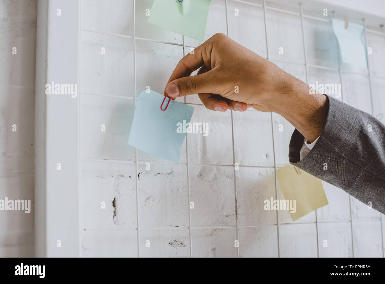 cropped image of businessman taking paper sticker from task board in office - Stock Image