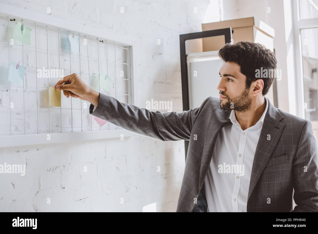handsome businessman putting paper sticker on task board in office - Stock Image