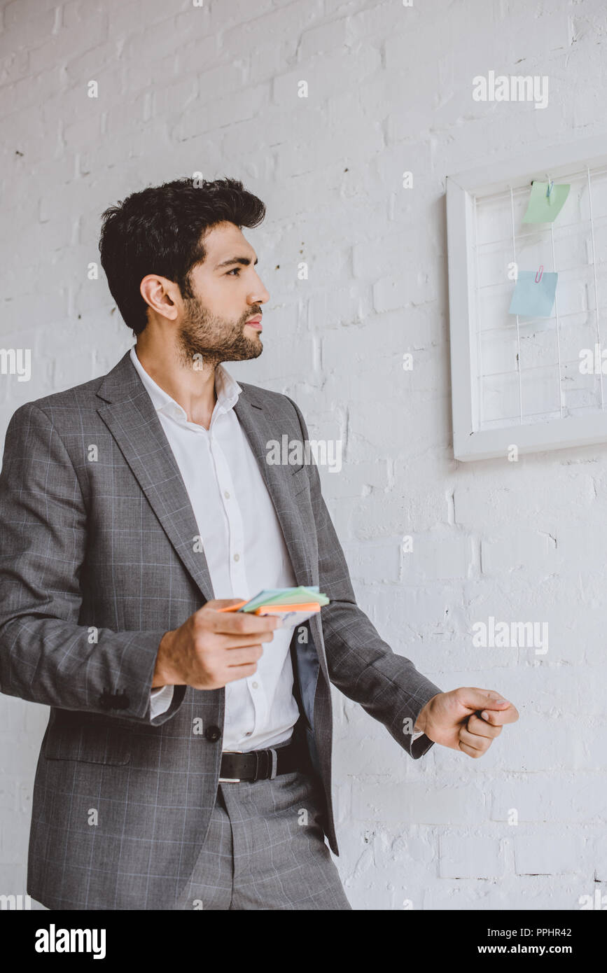 handsome businessman holding paper stickers and looking at task board in office - Stock Image