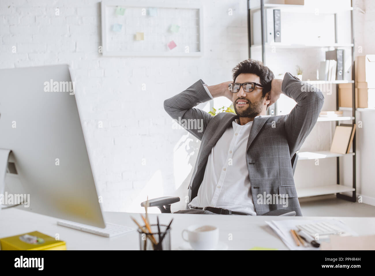 happy handsome businessman looking at computer with hands behind head in office - Stock Image