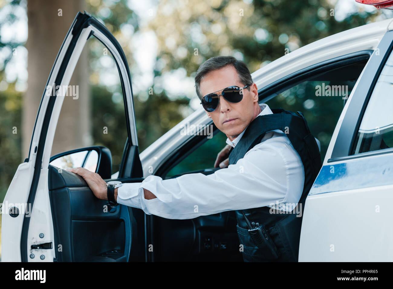 selective focus of mature policeman in bulletproof vest and