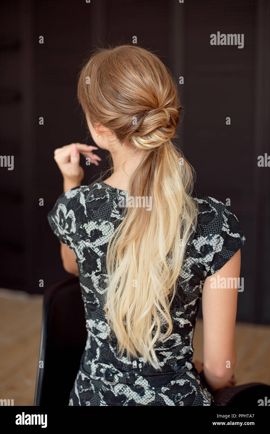 Unrecognizable rear view of woman hairstyle. Half-length back view of woman with slim waist and long hair wearing in sports style clothes - Stock Image