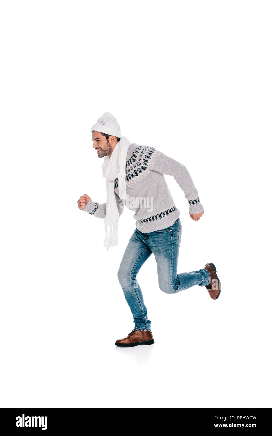 smiling young man in sweater, scarf and hat running and looking away isolated on white Stock Photo