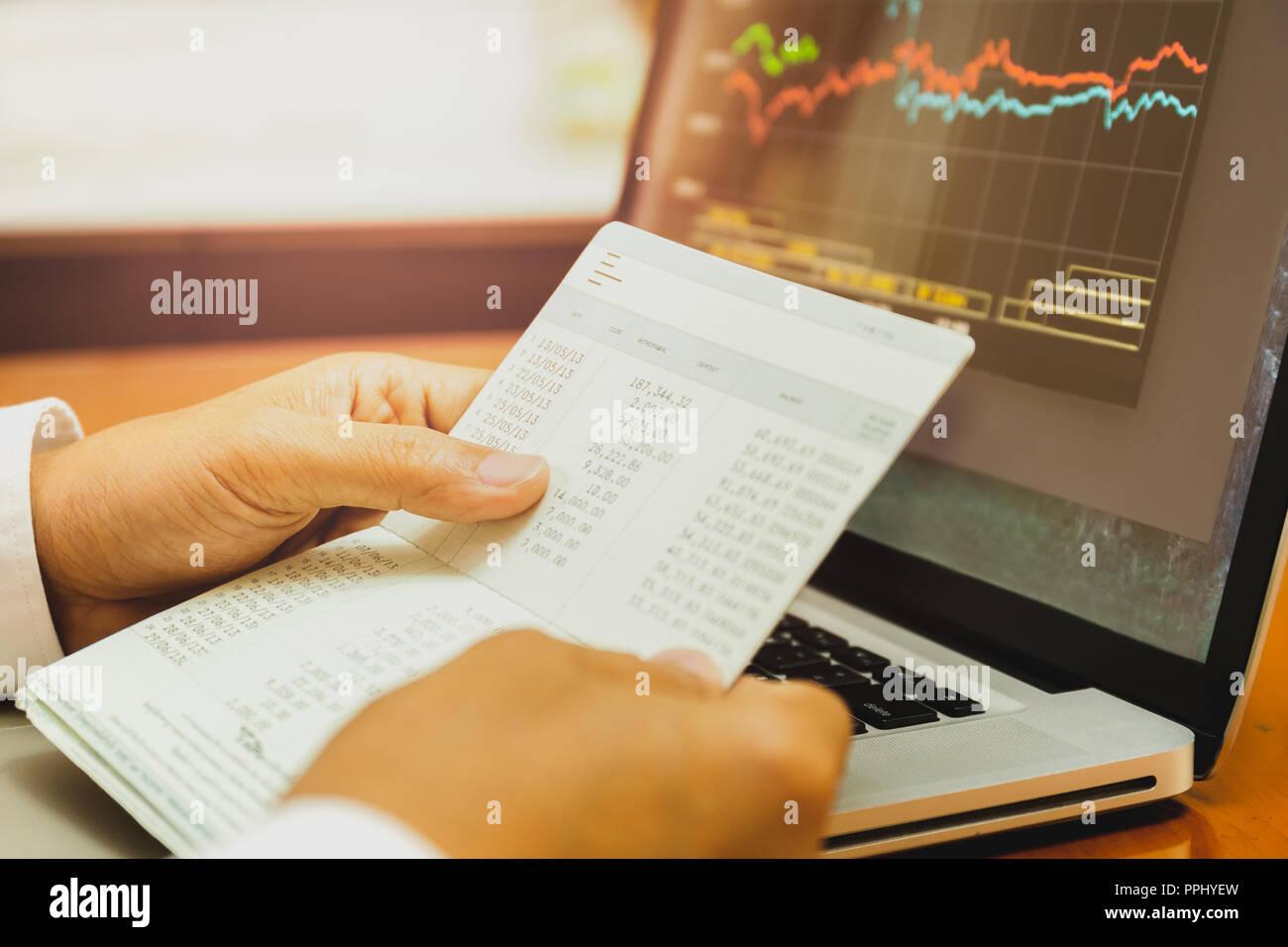 Businessman hands holding saving account passbook with stock money cahrt. - Stock Image