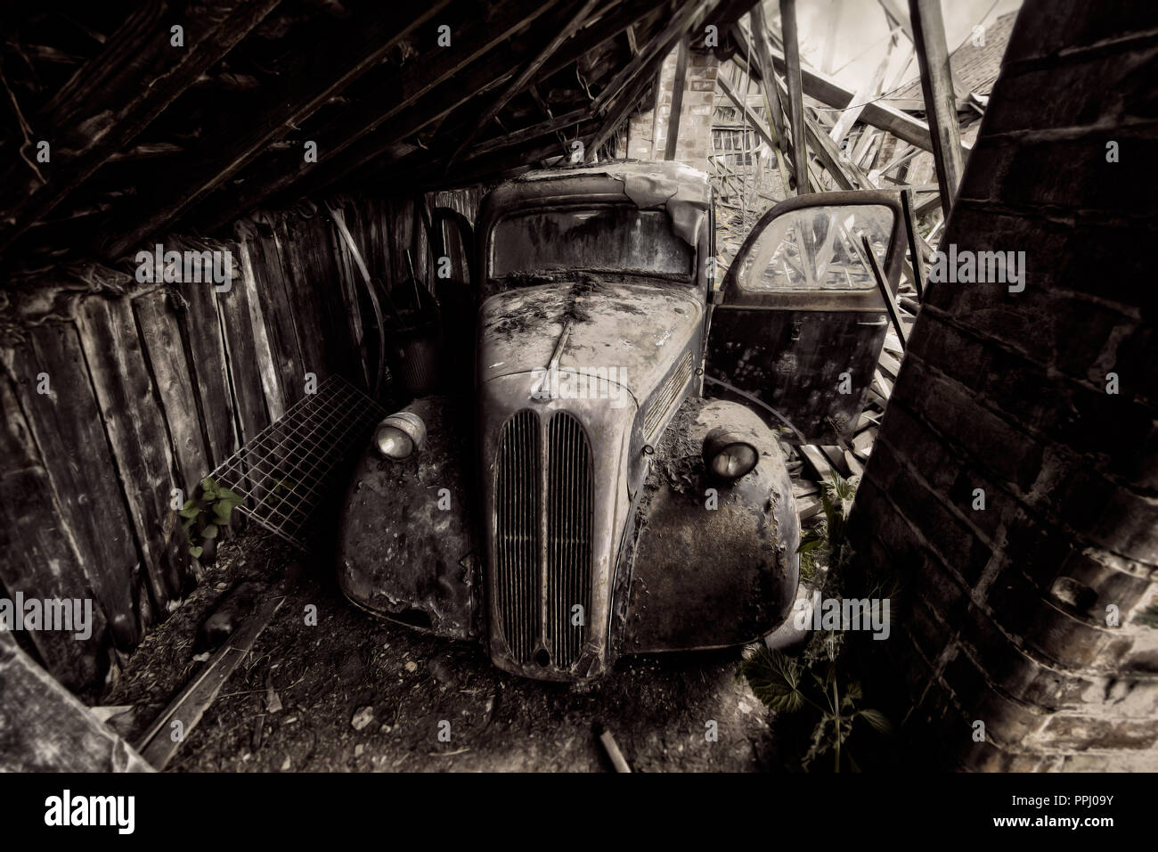 Abandoned old rusty classic car hidden in barn - Stock Image