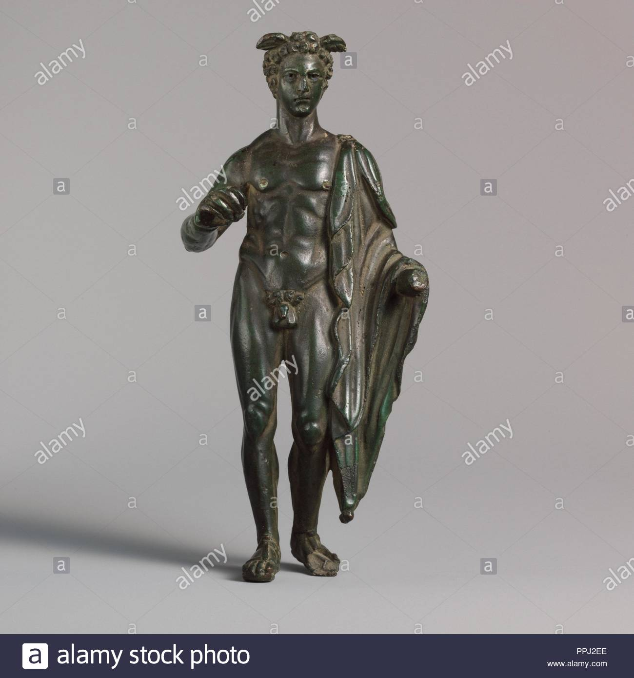 Bronze statuette of Mercury, Early Imperial, 1st century A.D., Roman, Bronze, Overall: 6 3/16 x 2 3/4 x 1 7/8 in. (15.7 x 6.9 x 4.8 cm), Bronzes, He stands with his weight resting on the right leg, with the left foot drawn back. - Stock Image