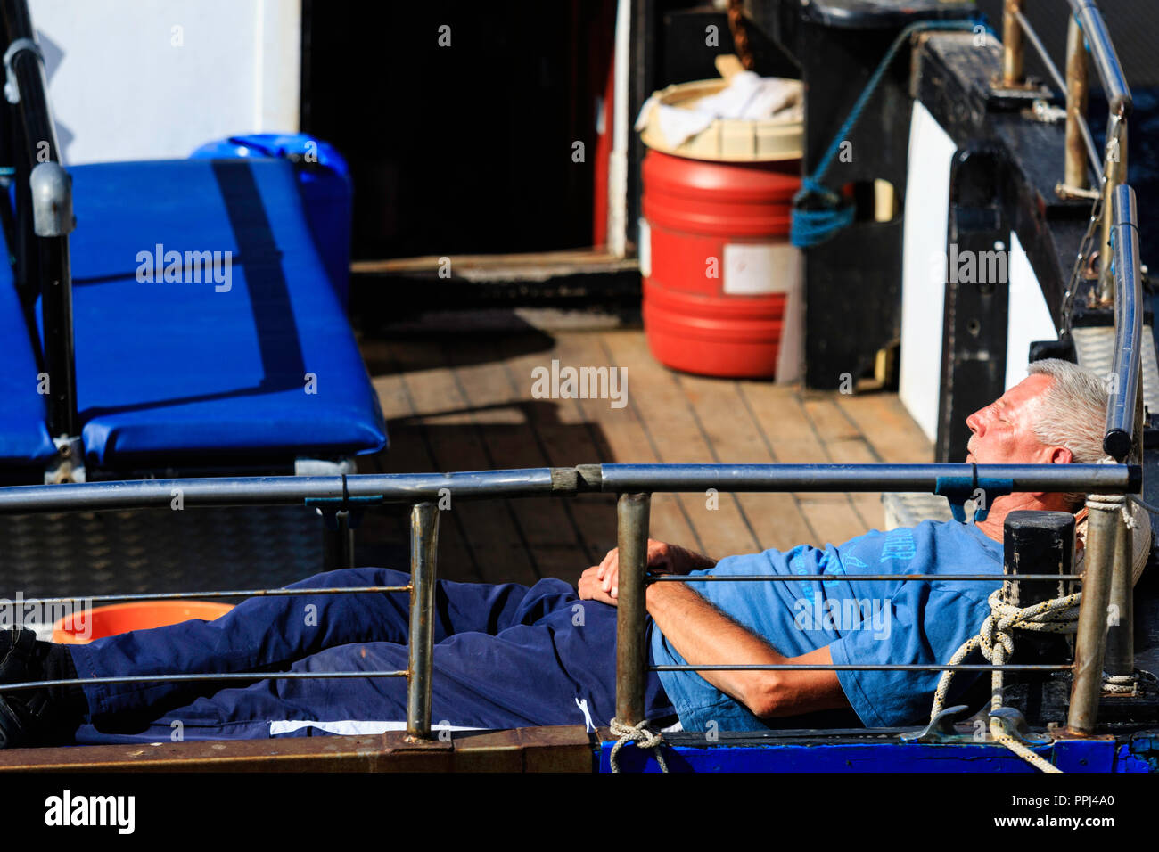 Candid of mature man asleep in the stern of his boat. Laying on his back in the summer sunshine - Stock Image