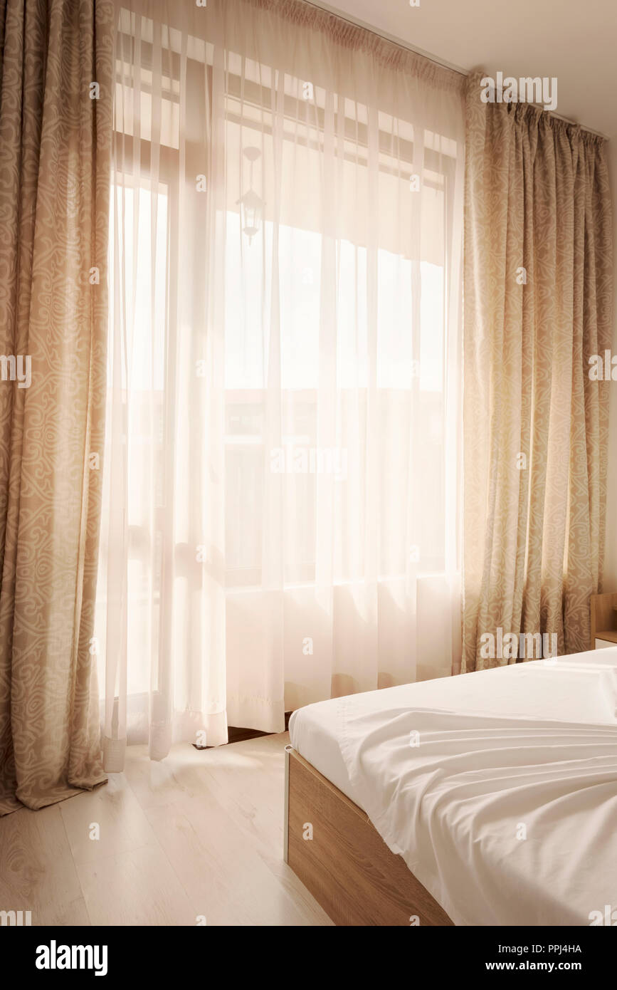 Hotel interior. Long beige curtains and tulle curtains, sheers on a window in the bedroom. Interior design concept. Stock Photo