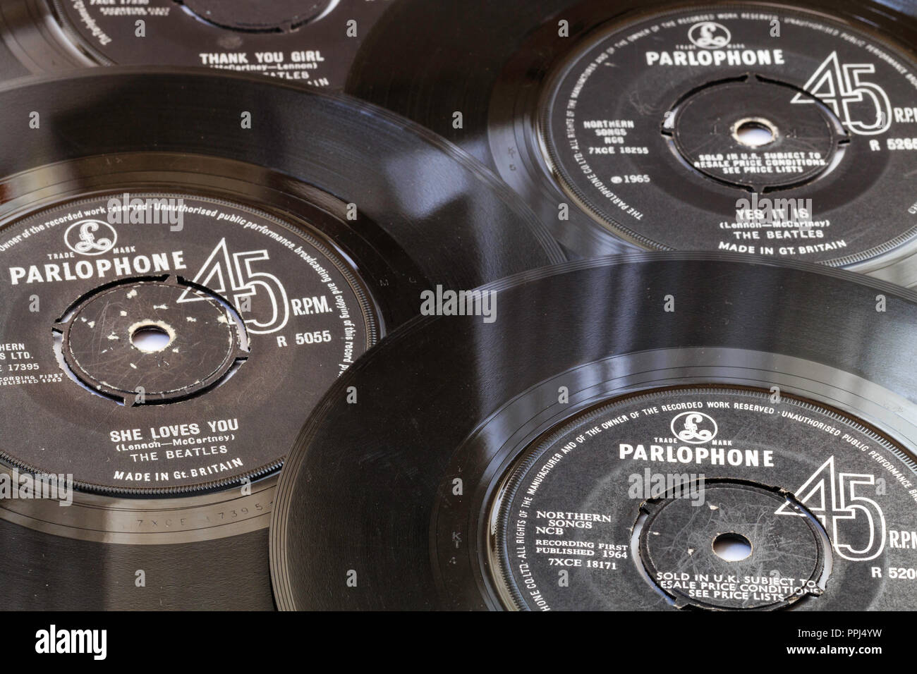 Four 45 rpm records, arranged. The Beatles, early 1960's hit singles. Parlophone label, 'She Loves You, I Feel Fine, Yes it Is' 'Thank you Girl' - Stock Image