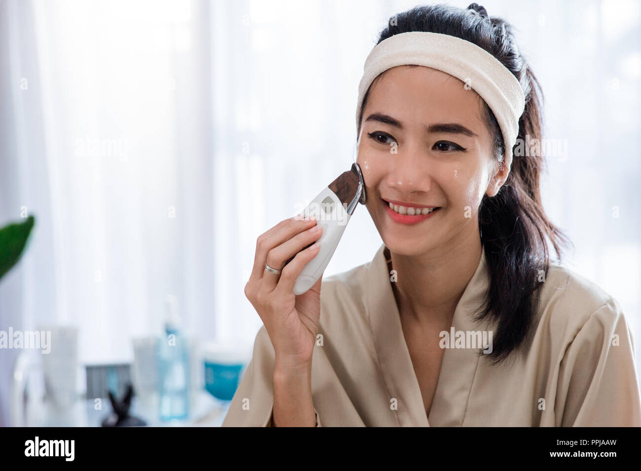 woman doing skin treatment her self  - Stock Image