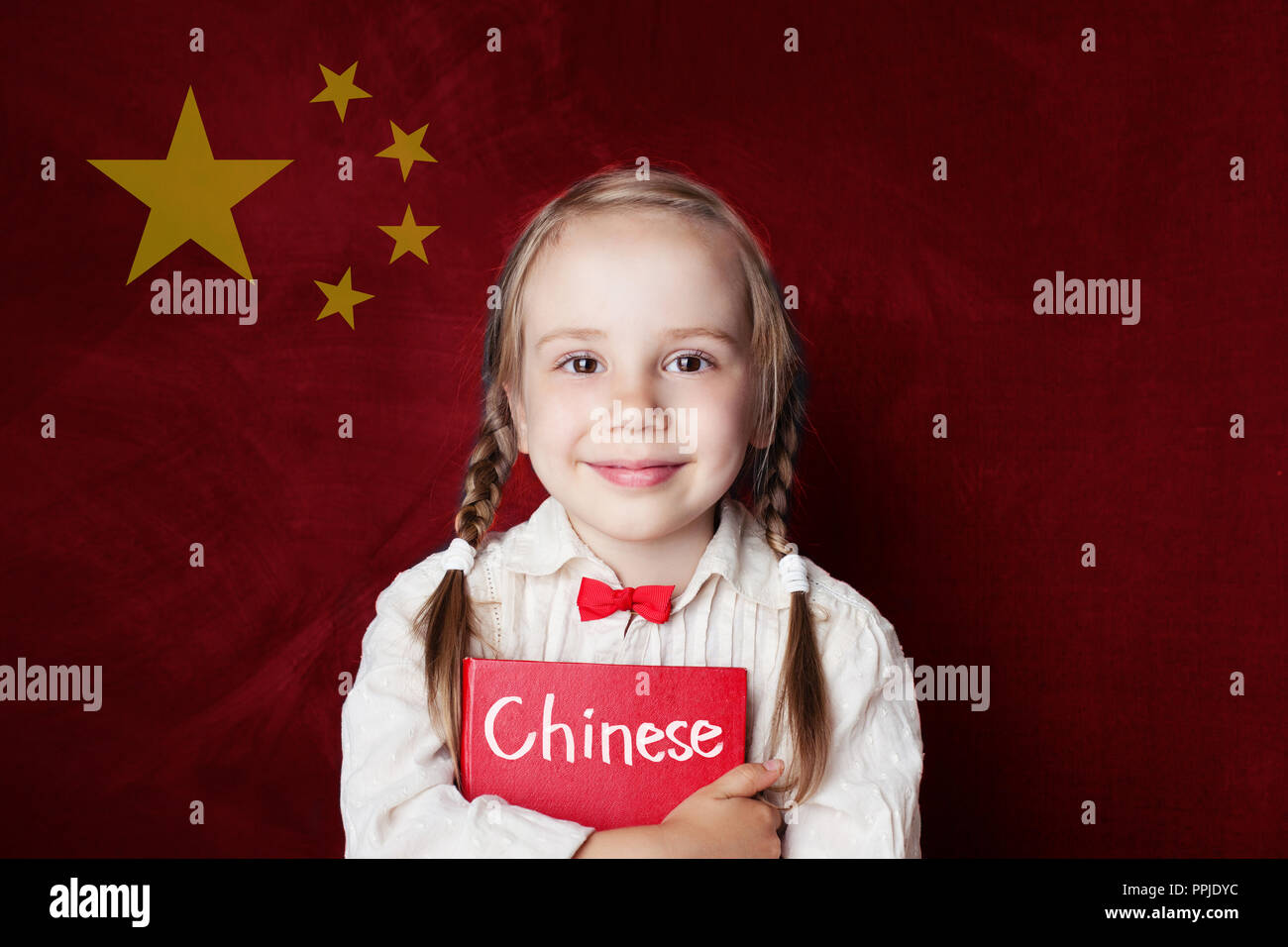 Chinese concept. Little girl student with book against the Chinese flag background. Learn language - Stock Image