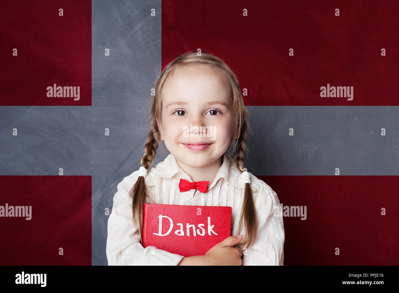 Danish concept. Child girl student with book against the Danish flag background. Learn language - Stock Image