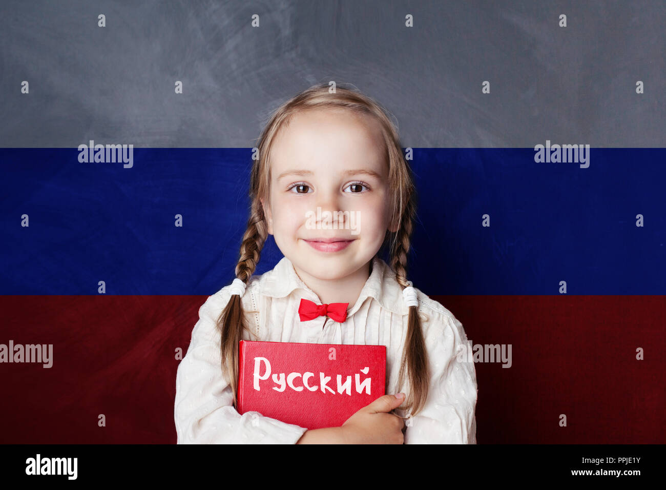 Learn russian language. Child girl student with book against the russian flag background - Stock Image