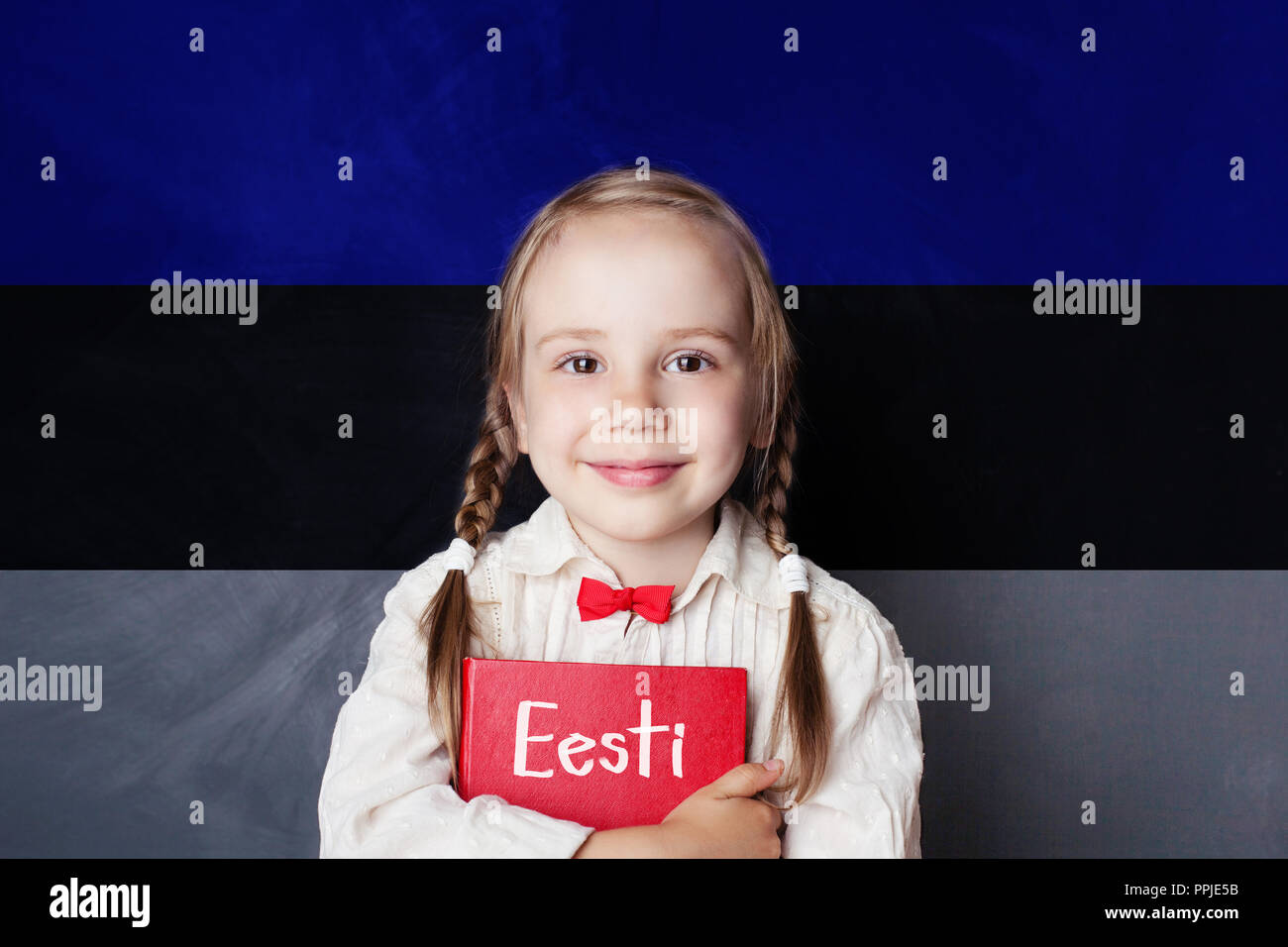 Estonian language concept with litte girl student with book against the Estonian flag background. Learn language - Stock Image
