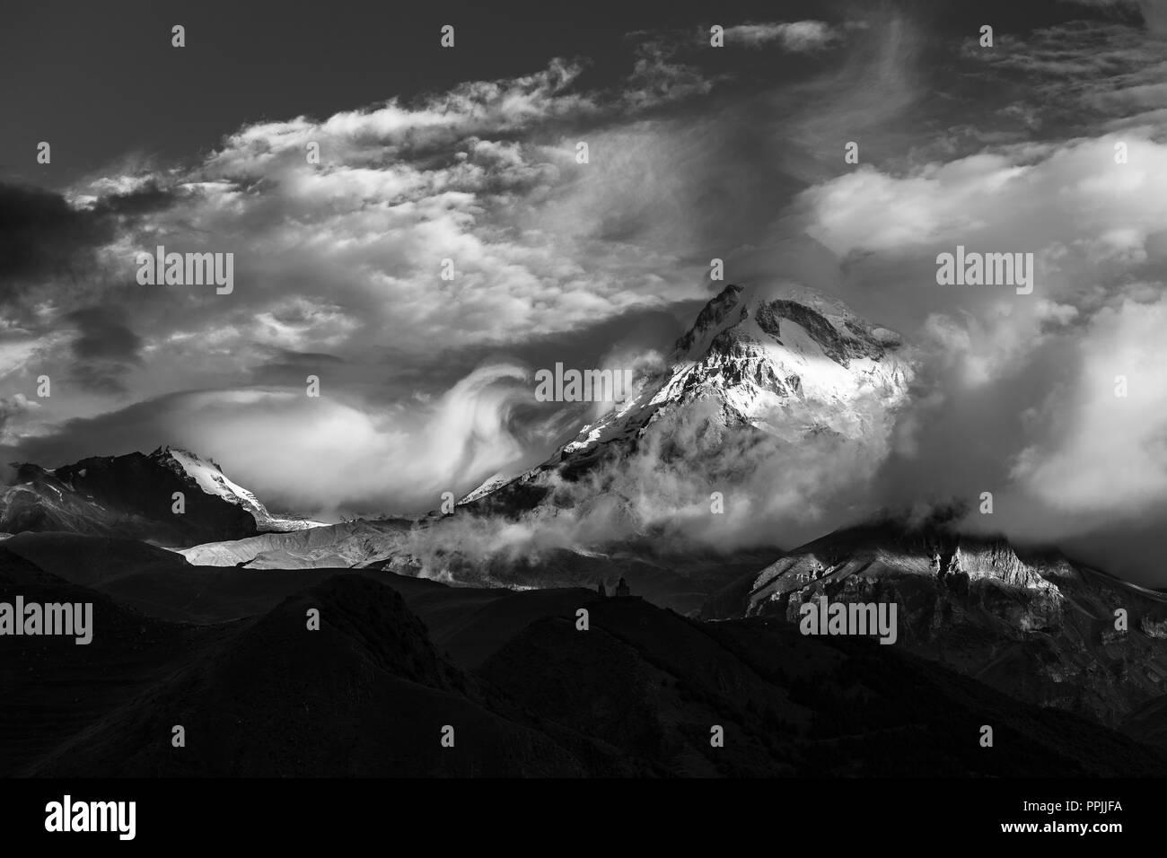 Kazbek top view from stepantsminda village. Georgia mountain peak. Black and white photo - Stock Image