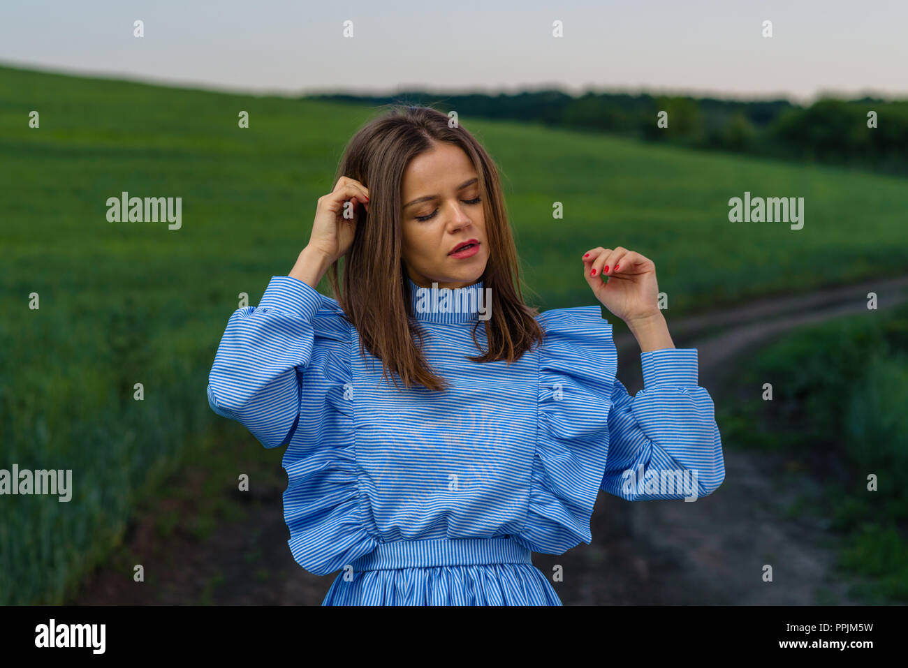 Young woman in blue and white striped dress is standing on the country road with her hands raised near field of green wheat during spring evening. Wom - Stock Image