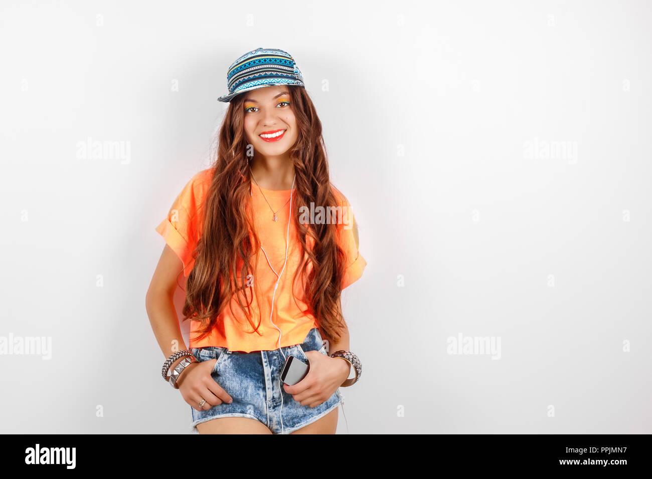 beautiful woman in sunglasses wearing in black hat and orange T-shirt  listening music near 99c05ef55836