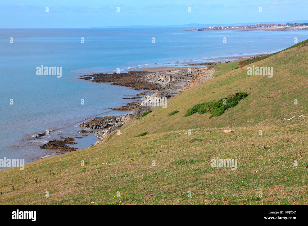A view from the clifftop looking down onto the rocky promontary and sandy beaches of Ogmore by sea with a low tide exposing the sands. - Stock Image