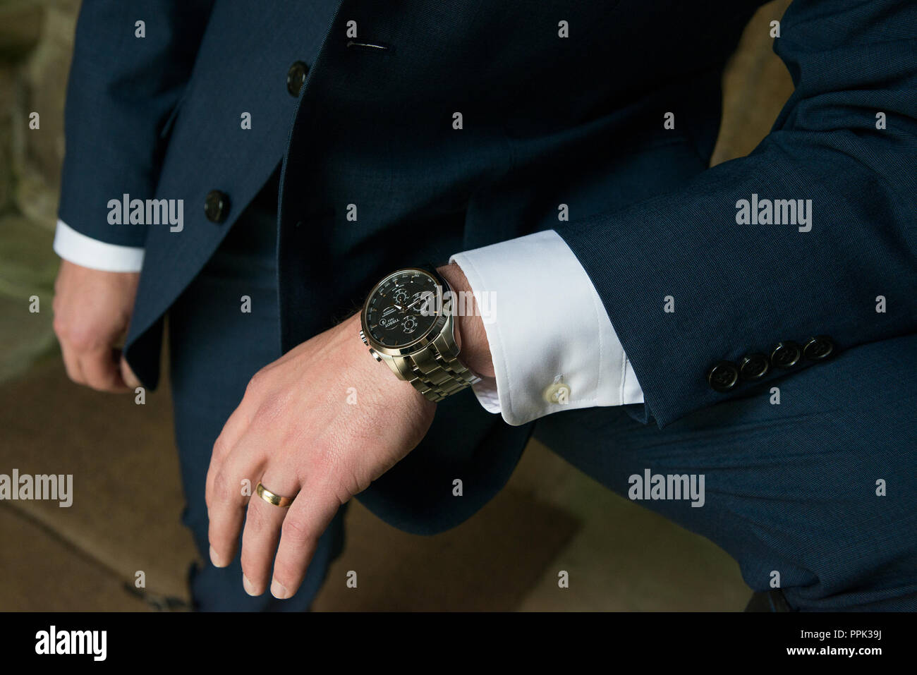 Young man's suited arm with shirt cuffs leaning across his raised knee to show his black faced Tissot watch and wedding ring. - Stock Image
