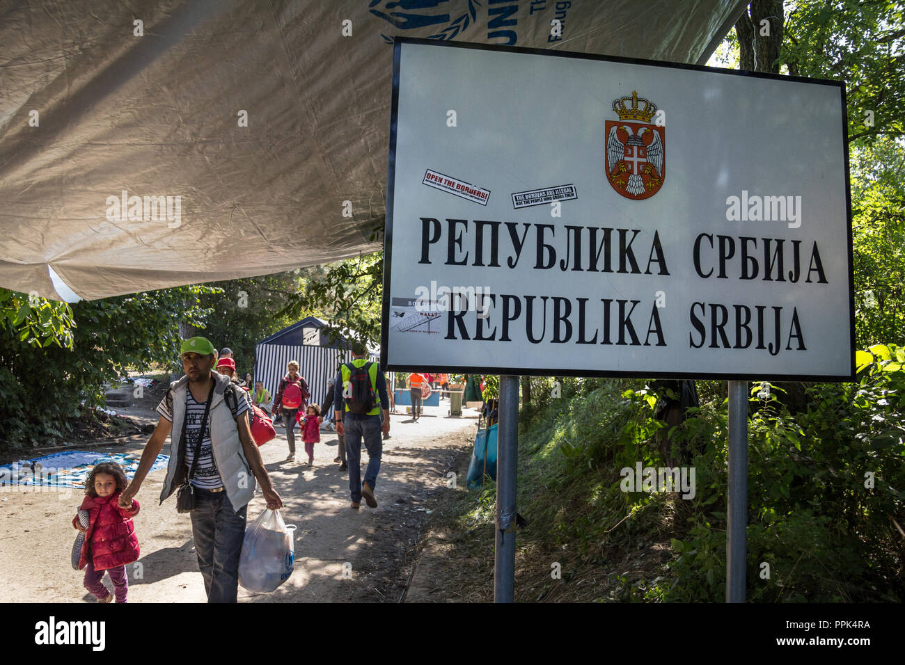 BERKASOVO, SERBIA - OCTOBER 3, 2015: Refugees walking next to the border sign on Serbia Croatia boundary in Berkasovo Bapska, on the Balkans Route, du - Stock Image