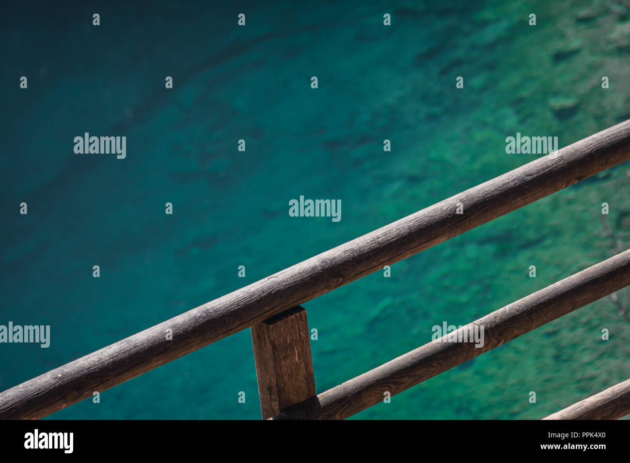 Wooden diagonal fence with blue lake in the background. Clear water, so you can see the stones on the ground. Minimalistic clean shot. - Stock Image