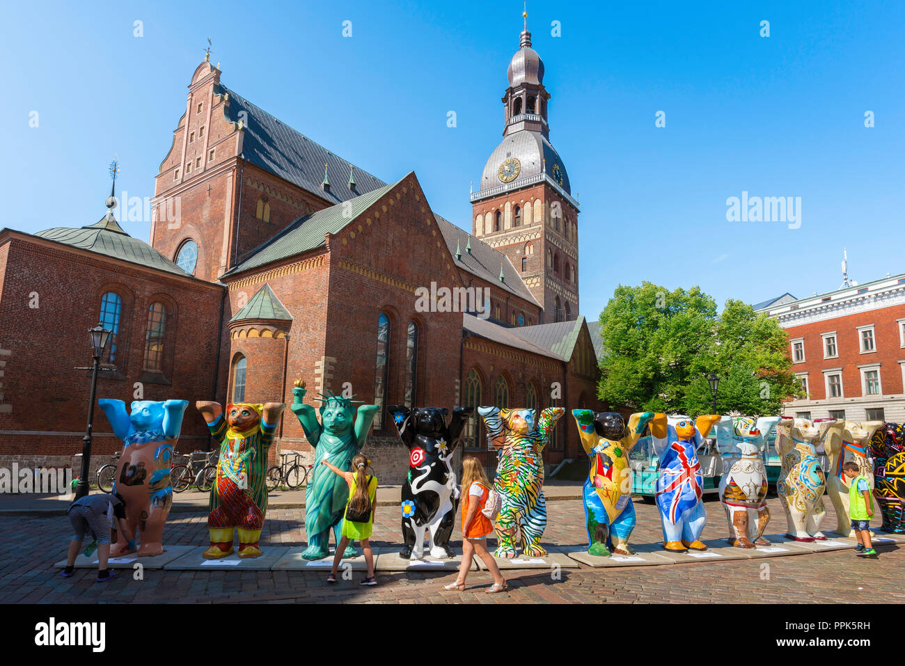 Riga Cathedral Square, against the backdrop of the Cathedral children view the United Buddy Bears exhibition sited in Riga Cathedral Square, Latvia. - Stock Image