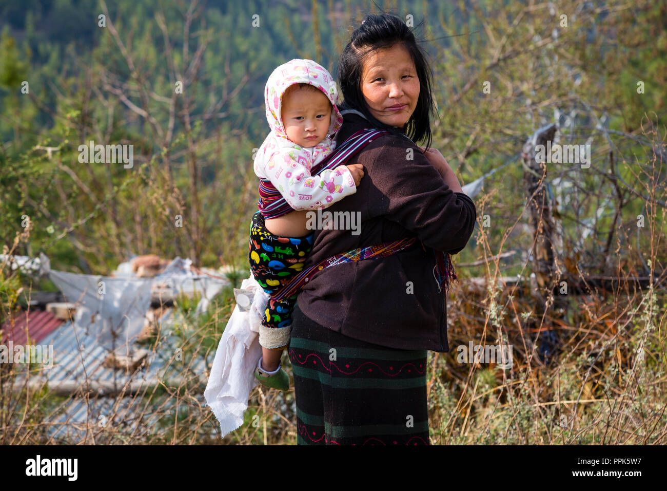 A Bhutanese local woman carries her baby on her back in Thimpu, the capital city of the Himalayan Kingdom of Bhutan - Stock Image