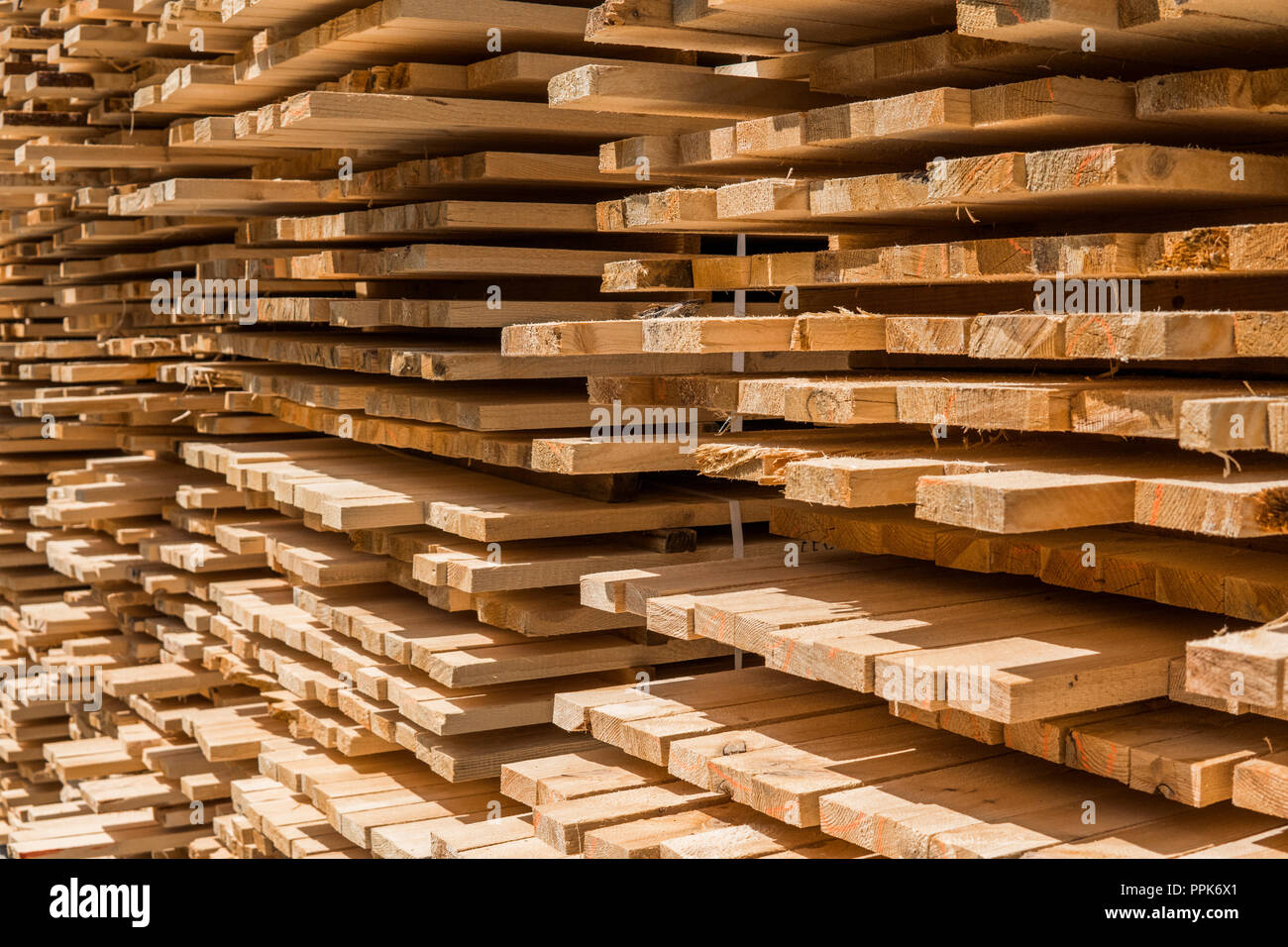 Piles of wooden boards in the sawmill, planking. Warehouse for sawing boards on a sawmill outdoors. Wood timber stack of wooden blanks construction material. Industry. Stock Photo