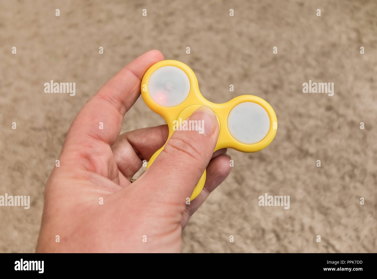 fidget spinner in a hand - not moving. - Stock Image