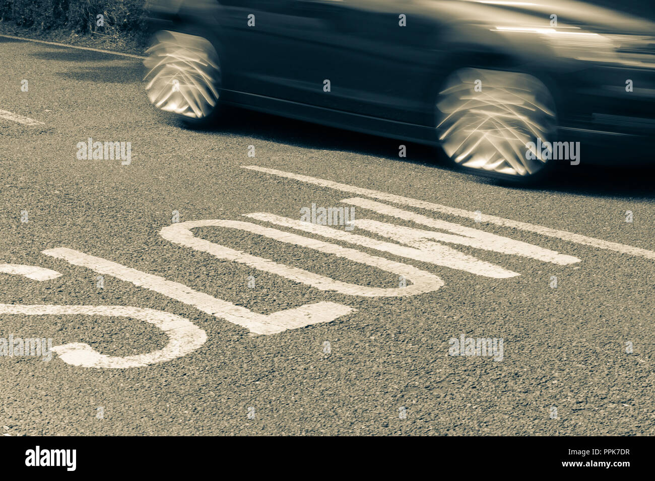 blurred car moving past road markings reading Slow Stock Photo