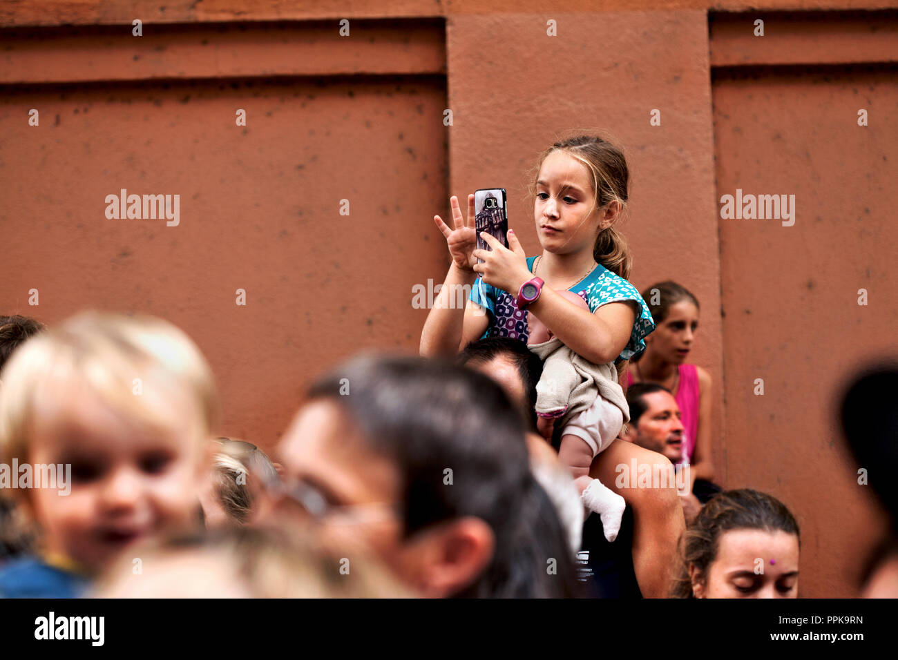 Young girls sitting on her father's shoulders using a smart phone. - Stock Image