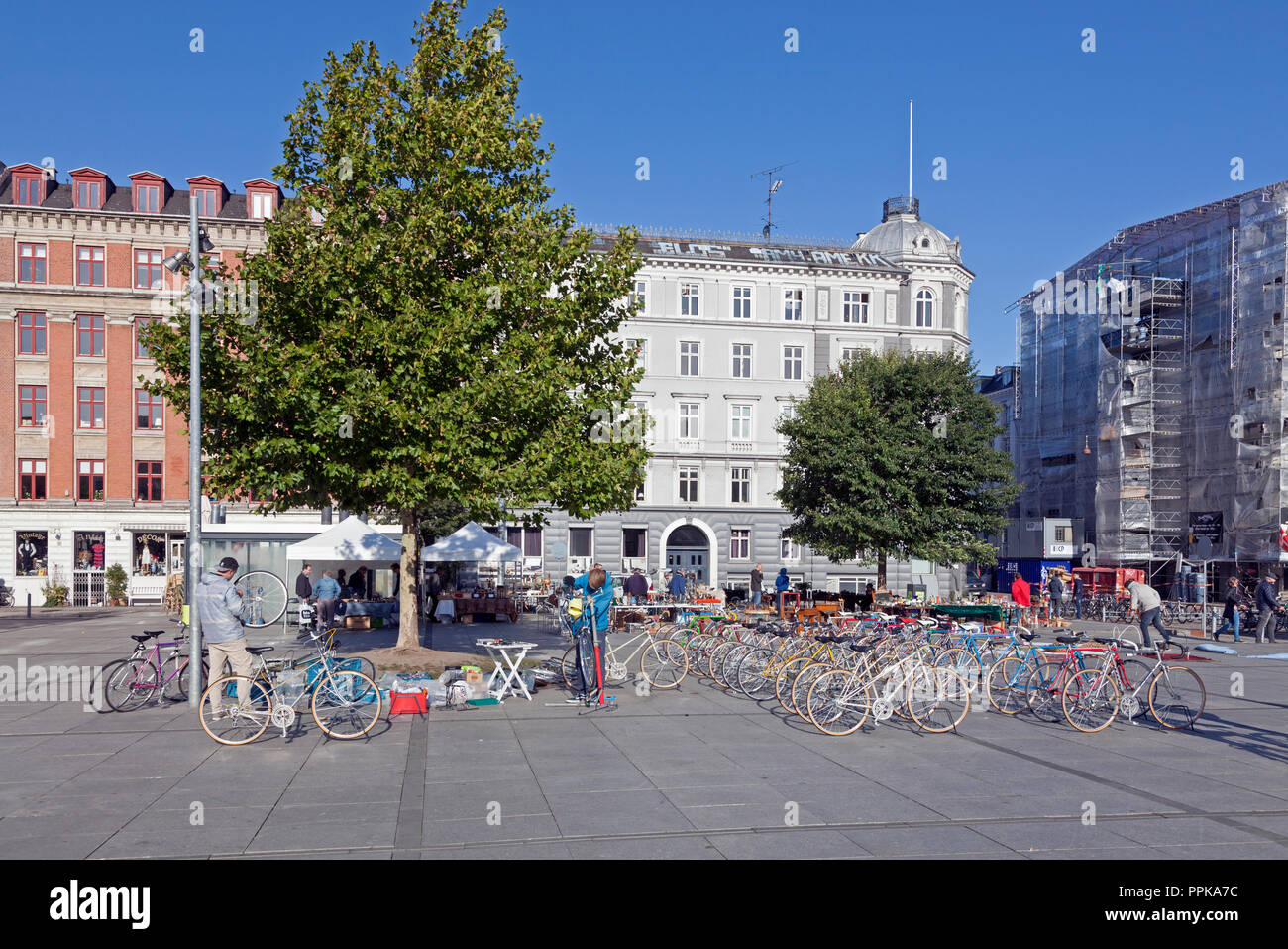 Young bicycle mechanics assembling and selling bicycles at a Saturday flea market on Israels Plads, Israels Square, in sunny autumnal Copenhagen. Stock Photo