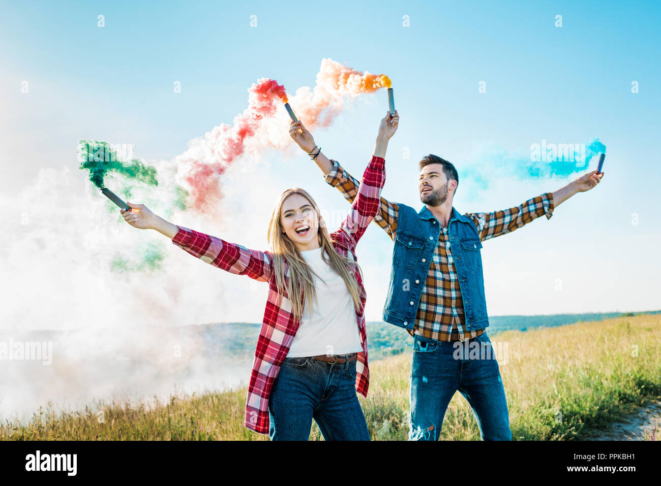 smiling young couple holding colorful smoke bombs on rural meadow - Stock Image