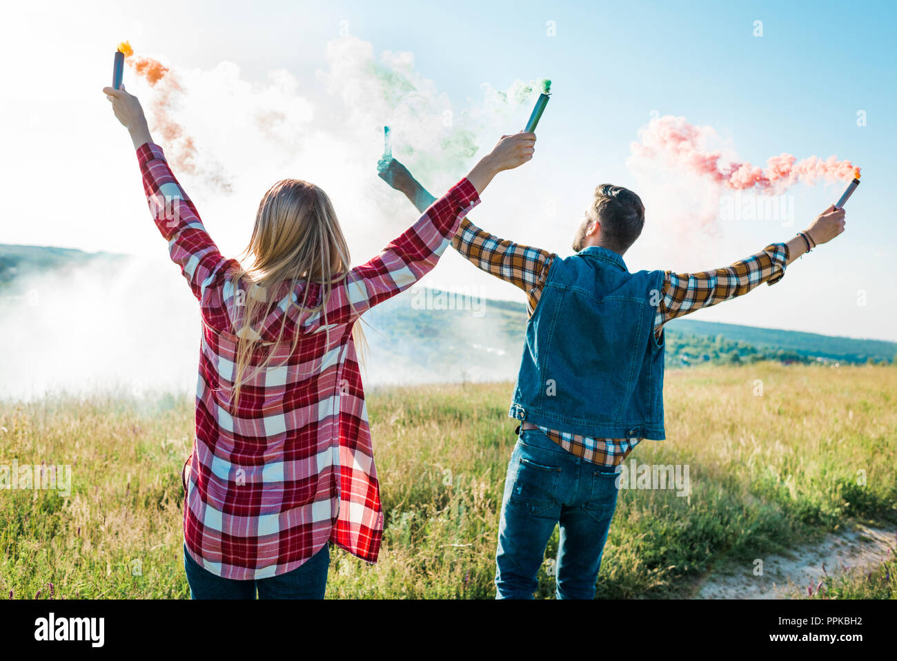 rear view of young couple holding colorful smoke bombs on rural meadow - Stock Image