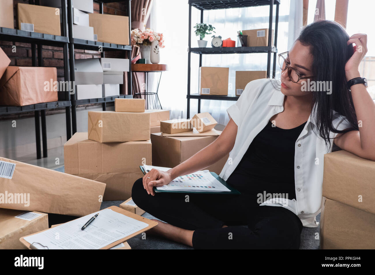Young woman with online business some trouble with shipping pack Stock Photo
