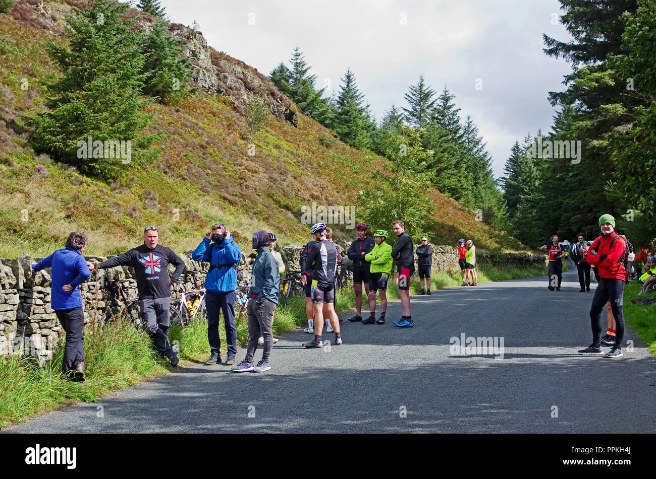 Cyclists and spectators wait patiently near the top of Whinlatter Pass, Cumbria, before the start of the Stage 5 Team Time Trial, Tour of Britain 2018 - Stock Image